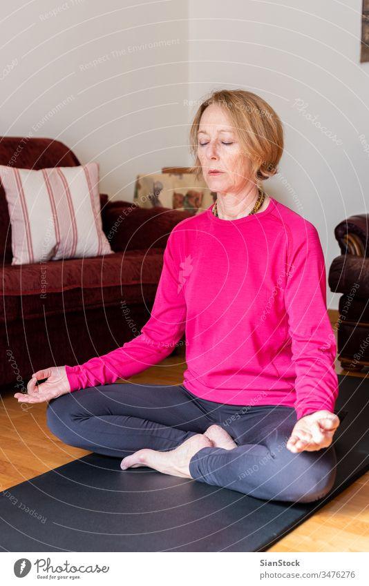 Frau mittleren Alters sitzt im Lotussitz auf einer Yogamatte in ihrem Wohnzimmer. Meditation Lotus-Pose Schönheit Training Europäer trainiert. Flexibilität