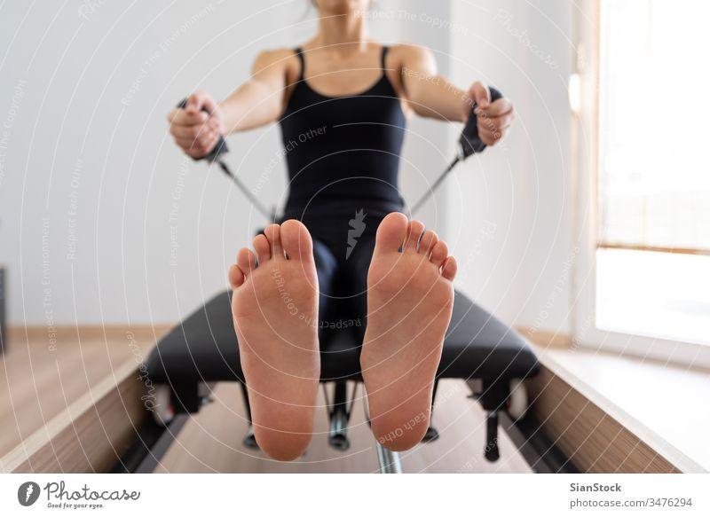 Junge Frau trainiert auf Pilates-Reformer-Bett, Füße in Nahaufnahme jung Mädchen Fitness Übung Fitnessstudio Gerät Training Gesundheit Körper Lifestyle