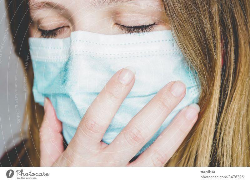 Junge Frau, die eine schützende Gesichtsmaske trägt Bund 19 COVID Grippe Mundschutz Coronavirus Pandemie Seuche Krankheit Atemwegserkrankungen soziale Distanz