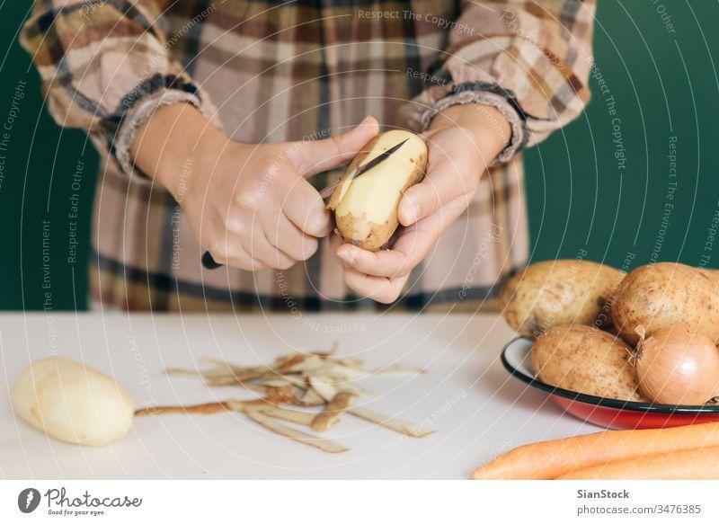 Frau schält in ihrer Küche Kartoffeln auf weißem Marmor ab, um ihr Essen zuzubereiten. sich[Akk] schälen Gemüse Veganer heimwärts peel-off angeblättert Karotten