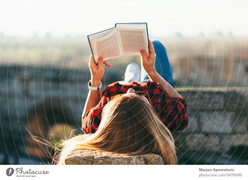 Junge Frau liest ein Buch im Freien jung lesen außerhalb Freude studierend Schüler genießend Lifestyle Frühling Sommer Lügen Freizeit Mädchen Menschen Person