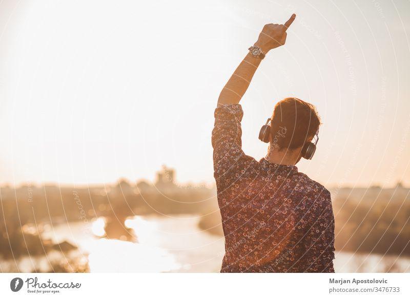 Junger Mann hört die Musik mit Kopfhörern bei Sonnenuntergang im Freien jung männlich Typ hören außerhalb genießend Freude freudig Tanzen Drahtlos
