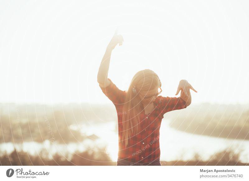 Junge Frau, die bei Sonnenuntergang im Freien mit Kopfhörern Musik hört jung hören außerhalb genießend Freude freudig Tanzen Drahtlos Technik & Technologie