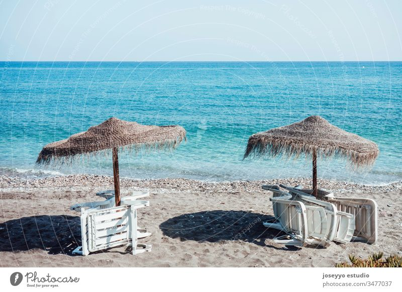Regenschirme und leere Liegestühle, die im Sommer am Strand gesammelt werden. Hintergrund Strandkorb blau Stuhl Küste Küstenlinie Coronavirus covid-19