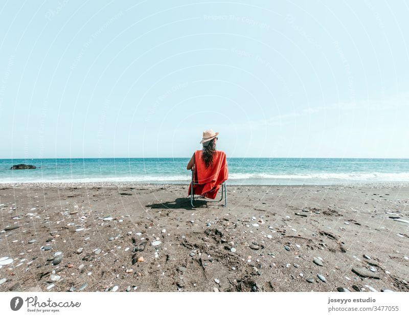 Mädchen mit Hut sitzt auf einem Liegestuhl mit orangem Handtuch am Strandufer Hintergrund schön blau Windstille Stuhl Küste Umwelt Frau Freiheit Behaarung