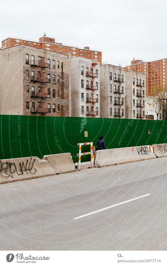 wohnhäuser in harlem, new york Straße Person Mensch gehen Häuser Verfall trist Wand Baustelle Hochhaus Wohnhaus urban Architektur Gebäude Stadt Haus Fassade