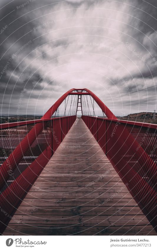 Rote Brücke mit einem langen Holzweg und einem Wolkenhimmel rote Brücke Brückengeländer Brückenkonstruktion Weg könnte Himmel Skyline Straßen Grauwert Spanien