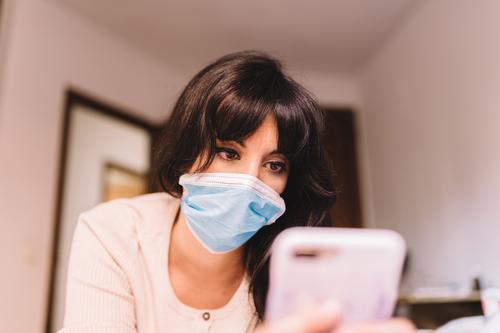 Frau zu Hause mit medizinischer Atemschutzmaske im Gesicht und Mobiltelefon. Chinesisches pandemisches Coronavirus, Virus Covid-19. Quarantäne, Konzept zur Infektionsprävention. Fokus auf ihr Gesicht.