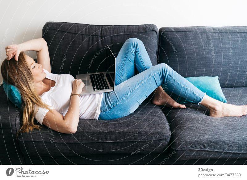 Ziemlich langhaarige Frau, die auf einem Sofa mit tragbarem Computer sitzt und von zu Hause aus arbeitet. benutzend Raum Erholung Lächeln Tippen Mitteilung