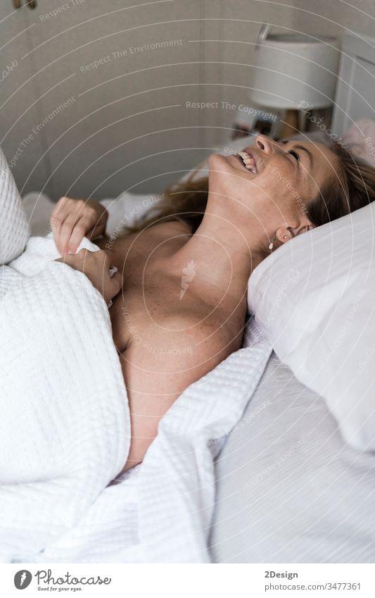 Porträt einer schönen erwachsenen Frau, die auf einem Bett liegt attraktiv Lügen Behaarung kurvenreich Mädchen Erwachsener Schönheit jung hübsch sinnlich