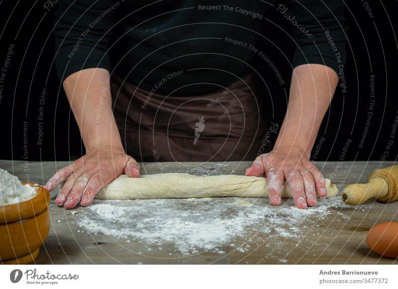 Männerhände kneten Brotteig auf einem Holztisch mit schwarzem Hintergrund Lebensmittel Mehl Weizen Mahlzeit Brotlaib Kochen organisch Feinschmecker