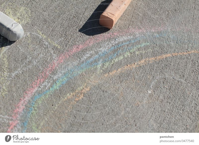 Regenbogen gemalt mit Straßenkreiden und zwei Straßenkreiden regenbogen malen kinderspiel freude kreativität corona symbolik draußen zeitvertreib Kinderspiel