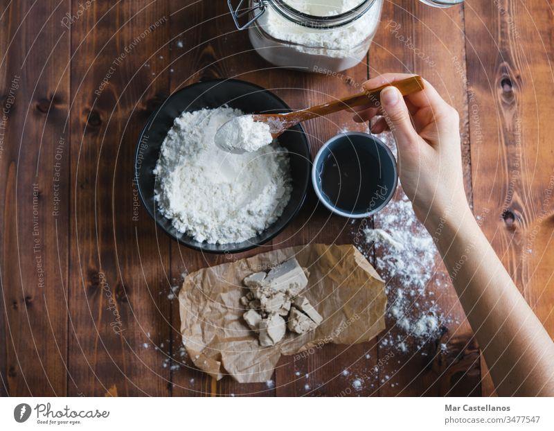 Eine Frauenhand fügt Mehl hinzu, um Sauerteig herzustellen. Konzept einer Bäckerei. Teigwaren kneten Löffel Hefe Verarbeitung Glasgefäß selbstgemacht Holzboden