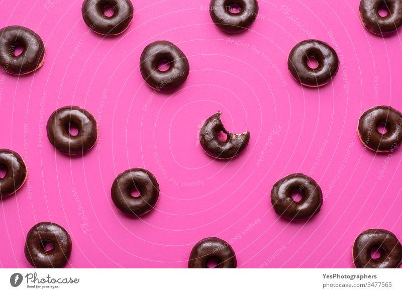 Donuts mit Schokolade glasiert Muster. Ein Doughnut mit fehlendem Biss obere Ansicht verbündet Hintergrund Bagel Bäckerei gebissen Kalorien Kohlenhydrate schoko