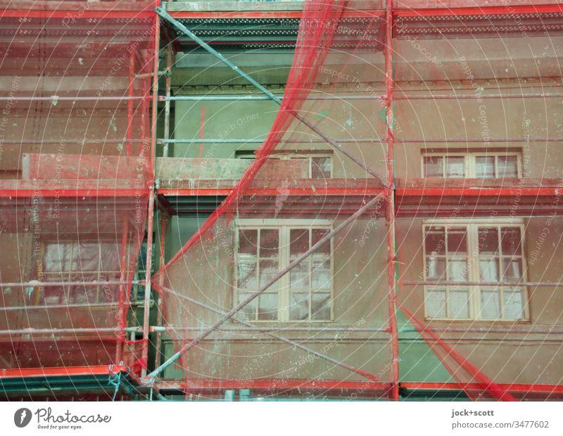 Renovierung der grünen Fassade mit rötlichen Baugerüst Baustelle Abdeckung bauen authentisch Stimmung Schutz Wandel & Veränderung Modernisierung Architektur Tag