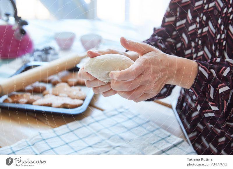 Weibliche Hände einer älteren Frau kneten den Teig. Oma backt Kekse. Heller Hintergrund. Teigwaren Senior Mehl alt Tisch heimwärts Küche Bäcker gealtert
