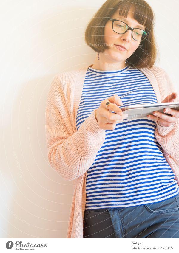 Lächelndes Mädchen mit Brille mit Tablette benutzend Smartphone Mobile Arbeit von zu Hause aus stayhome lernen Frau Schüler Beteiligung Business Behaarung