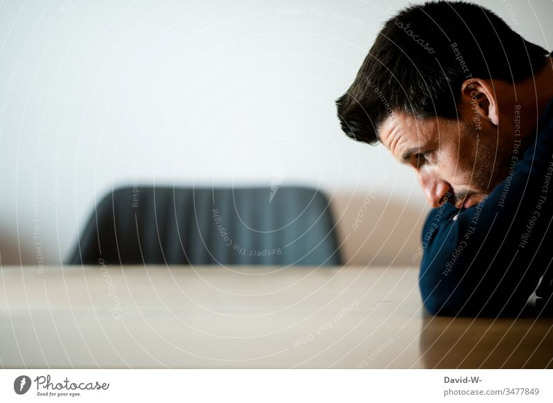 junger Mann in Gedanken versunken hockt an einem Tisch Junger Mann hocken sitzt sitzen denken nachdenken überlegen nachdenklich Porträt Textfreiraum oben Stuhl