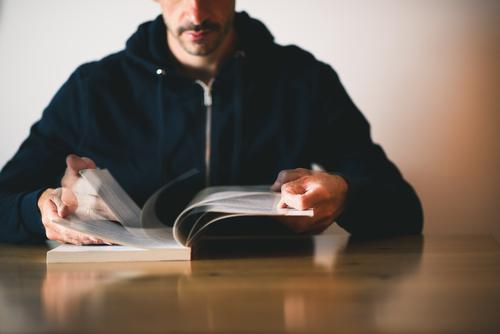 Mann liest ein Buch und blättert Seiten um etwas nachschlagen lesen Bewegung blättern umblättern Schreibtisch Tisch Wissen lernen Buchseite Nachschlagen anonym