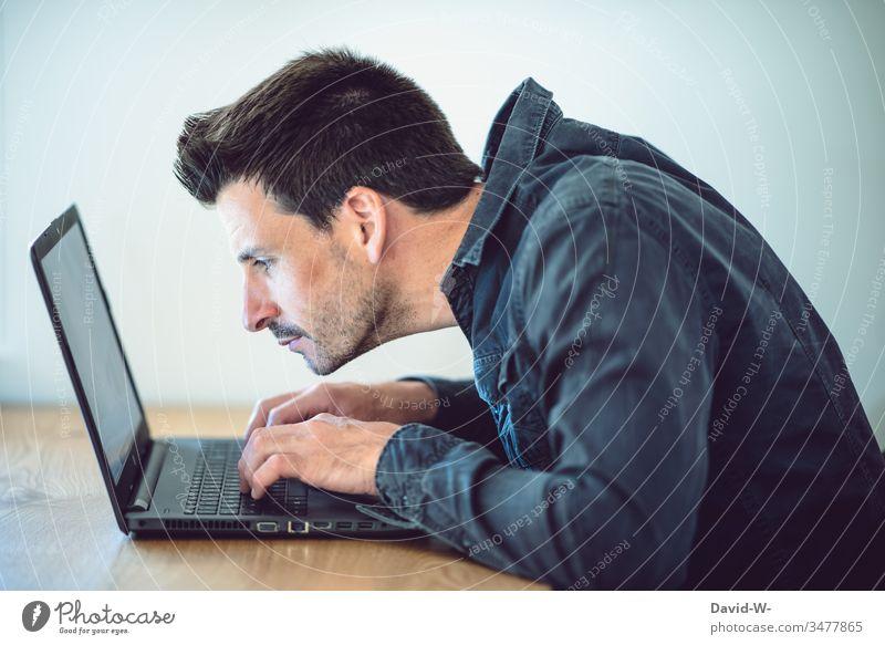Mann arbeitet konzentriert am Laptop haltungsschäden rückenschmerzen ungesund Körperhaltung Arbeitsplatz laptop arbeiten Büro Schreibtisch Tisch Business