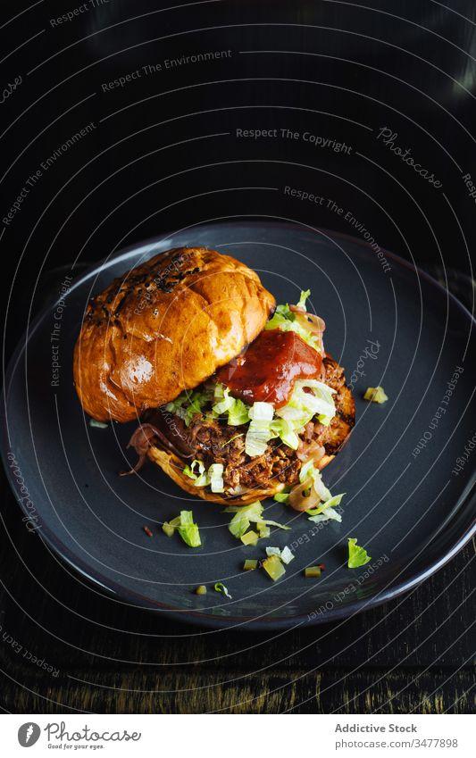 Hamburger mit Ketchup und Kräutern Feinschmecker Burger Brötchen Kraut Saucen Fleisch Teller dienen Lebensmittel Mahlzeit lecker geschmackvoll Mittagessen Küche
