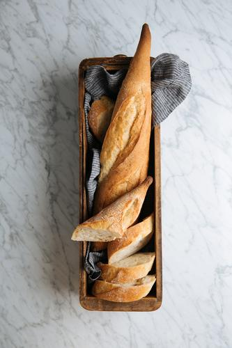 Frisch geschnittenes Brot auf Holztablett Baguette frisch Scheibe Tablett Tisch Bäckerei Brotlaib Kruste selbstgemacht Kunstgewerbler hölzern Murmel