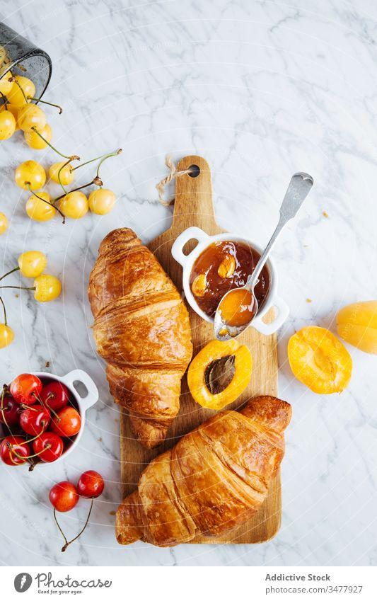 Croissant und Aprikosenmarmelade auf Holzbrett Marmelade Gebäck Frühstück backen frisch natürlich Morgen Lebensmittel dienen lecker geschmackvoll Mahlzeit