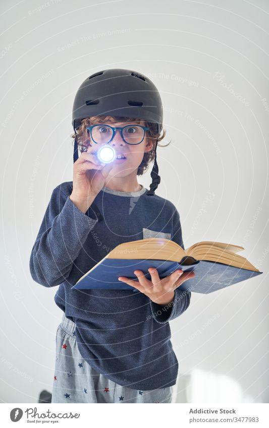 blondes Kind im Schlafanzug mit einem Helm, einer Taschenlampe und einem Buch, das Forschung spielt Kinder Schutzhelm Spiel behüten Fröhlichkeit Genuss spielen