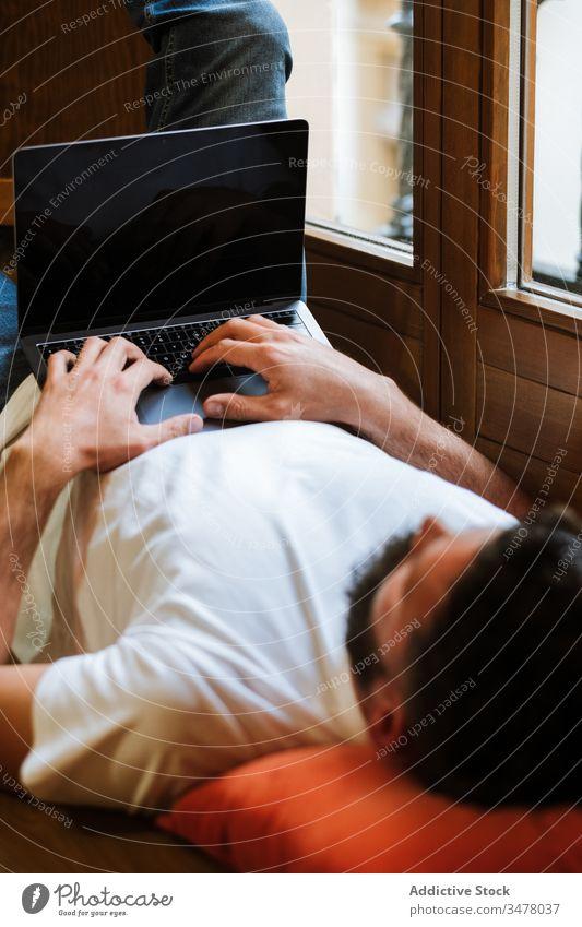 Freiberufler mit Laptop zu Hause Mann freiberuflich Lügen benutzend heimwärts Tippen trinken Stock Projekt modern männlich lässig Gerät Arbeit Internet