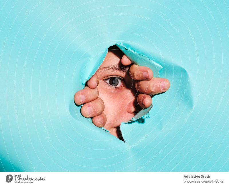 Kind guckt durch Loch im Papier Golfloch schauen Sie spionieren neugierig zerrissen Konzept Auge Finger Tierhaut beobachten Interesse zuschauen geheim Aussehen