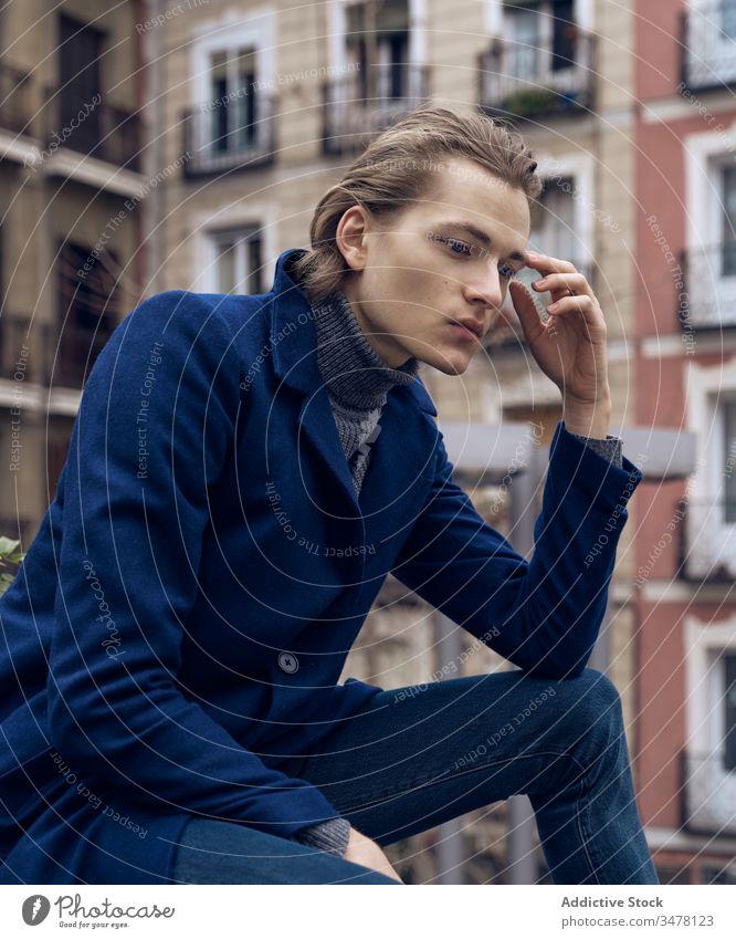 Nachdenklicher Mann in modischer Kleidung sitzt auf der Straße besinnlich nachdenklich Stil trendy ernst Denken urban Großstadt jung männlich elegant modern