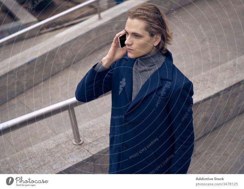 Trendy Mann benutzt Handy in der Stadt Smartphone benutzend Stil trendy ernst urban Stein Straße Apparatur Gerät Mobile Anschluss Großstadt Internet elegant