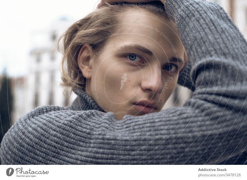 Selbstbewusster junger Mann schaut in die Kamera trendy ernst selbstbewusst Straße modern Stil Pullover gutaussehend urban Großstadt lässig Zeitgenosse Mode