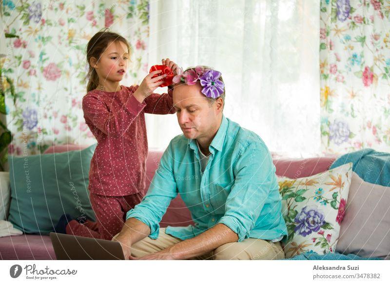 Kind spielt und stört Vater, der fern von zu Hause arbeitet. Kleines Mädchen, das Papas Haare kämmt und eine Frisur macht. Mann sitzt mit Laptop auf der Couch. Familie verbringt Zeit miteinander im Haus.
