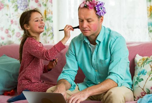 Kind spielt und stört Vater, der fern von zu Hause arbeitet. Kleines Mädchen, das mit einem Pinsel Schminke aufträgt. Mann sitzt mit Laptop auf der Couch. Familie verbringt Zeit miteinander im Haus.