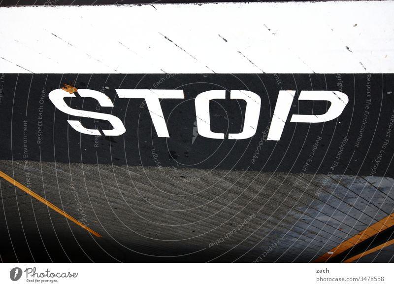 Aufschrift auf einer Straße - STOP Buchstaben Wand Fassade Zeichen Mauer Textfreiraum unten Schriftzug Graffiti Schriftzeichen Textfreiraum oben Gebäude