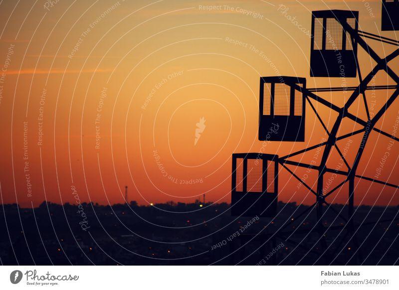 Altes Riesenrad im Sonnenuntergang über einer Stadt alt Schatten Silhouette orange gelb Himmel Außenaufnahme Menschenleer Abend