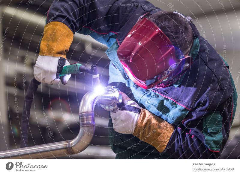 Industriearbeiter beim Schweißen in einer Metallfabrik. Schweißer Arbeiter inox Stahl Tube Kunsthandwerker industriell Handwerk Herstellung Maschinenbau