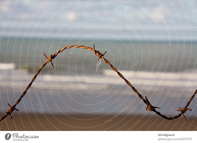 Strand betreten verboten! Rostiger Stacheldraht im Sonnenlicht am Nordseestrand in Ostende (Belgien). Zum Schutz der Batterie Aachen im WWII am Atlantikwall.