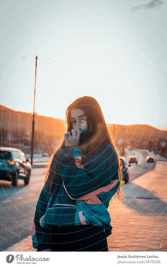 Mädchen mit Oldtimer-Kleidung mit Autos und einem schönen Sonnenuntergang im Hintergrund Leben altehrwürdig Vintage-Mädchen Porträt Straße Model niedlich