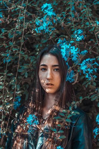 Junges Mädchen umgeben von blauen Blumen Vorderansicht Oberkörper Porträt mehrfarbig Innenaufnahme Unschärfe Farbfoto Kopf Dame attraktiv lange Haare Menschen