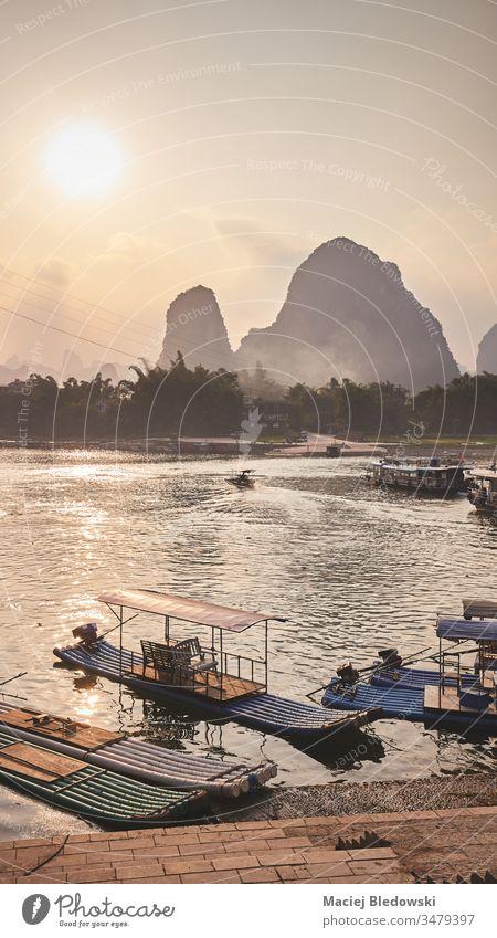 Bambusflöße am Ufer des Li-Flusses in Xingping bei Sonnenuntergang, China. Lijang Fluss Floß Boot reisen Asien schön Abenddämmerung gefiltert Hügel Karst