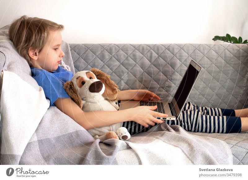 Online-Fernunterricht zu Bildung und Arbeit. Kinder lernen fern von zu Hause auf der Couch. Jungenhände halten Laptop Entfernung online Schule Lernen heimwärts