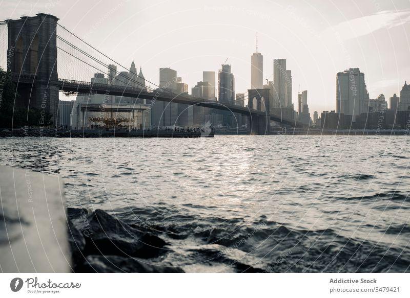 Moderne Stadtlandschaft mit Brücke über den Fluss am Abend Großstadt Wolkenkratzer Stadtbild New York State Sonnenuntergang Gebäude urban Architektur Brooklyn