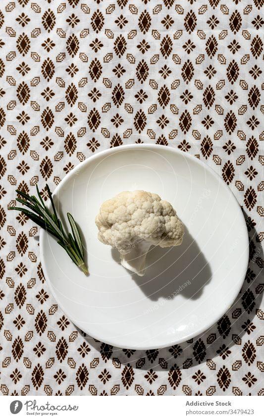 Rohes Blumenkohlbouquet mit Rosmarin im Sonnenlicht Entzug Mahlzeit Gemüse Küchenkräuter gesunde Ernährung Veganer Diät niemand Ast Antioxidans Scheibe