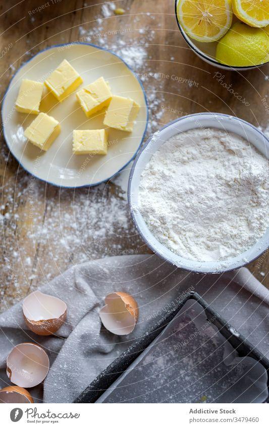Zutaten für Kuchenrezept auf dem Tisch mit Mehl gepudert Bestandteil Butter Rezept Eier backen Zitrone Lebensmittel Vorbereitung Bäckerei selbstgemacht