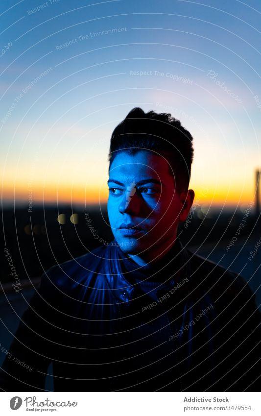Stilvoller junger Mann abends auf der Straße dunkel Sonnenuntergang trendy Dämmerung Abenddämmerung Farbe ernst selbstbewusst rot blau männlich Frisur