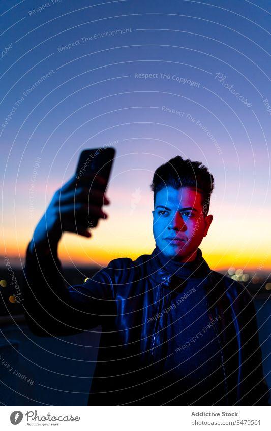 Junger Mann nimmt sich abends selbst die Zeit Smartphone Selfie neonfarbig Handy Sonnenuntergang dunkel blau Licht Himmel Stil ernst Farbe Apparatur Gerät