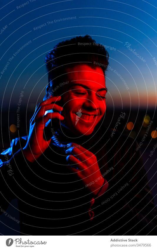 Hübscher Kerl telefoniert auf nächtlicher Straße Mann neonfarbig Smartphone reden dunkel rot blau modern Nacht Gerät leuchten Apparatur Mitteilung selbstbewusst