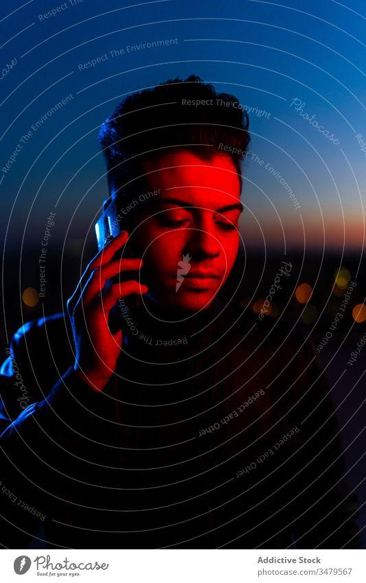 Hübscher Kerl telefoniert auf nächtlicher Straße Mann neonfarbig Smartphone reden dunkel rot blau modern Nacht ernst Gerät leuchten Apparatur Mitteilung